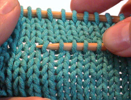 Notice she picks up the RIGHT LEG of each stitch so that they will be sitting properly on the new needle when the above rows are removed.